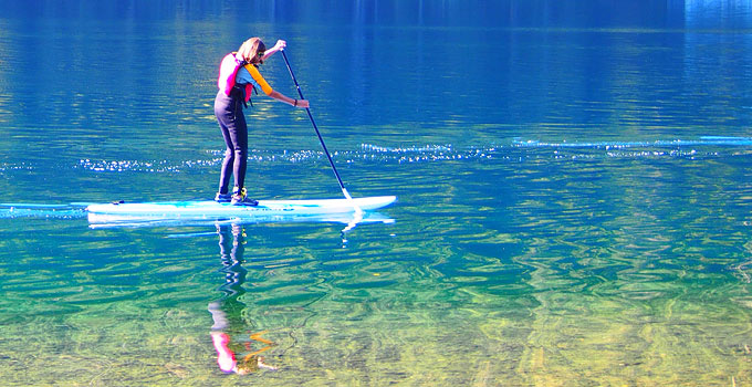 a woman stand up paddleboarding at Lake Crescent, Olympic National Park